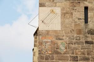 Sonnenuhr am Südturm mit dem Wappen der Ansbacher Marktgrafenund der Stadt Ansbach. Über der Sonnenuhr: Baumeistermaske